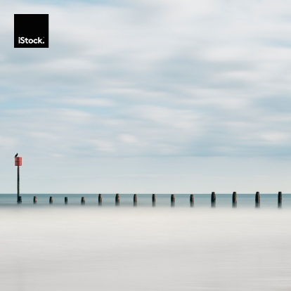A 42 second long exposure of the groynes on Blyth Beach, Northumberland, UK. A seabird sits on furthest post. The breaking waves have turned into silky smooth white and the clouds movement is blurred. Posts are sharp and the bird has remain virtually unmoved in the time (slight blur to head and tail).